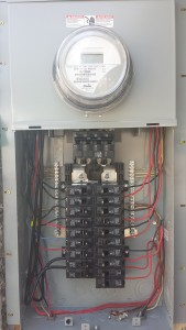 Open electrical panel box with exposed switches and wires.