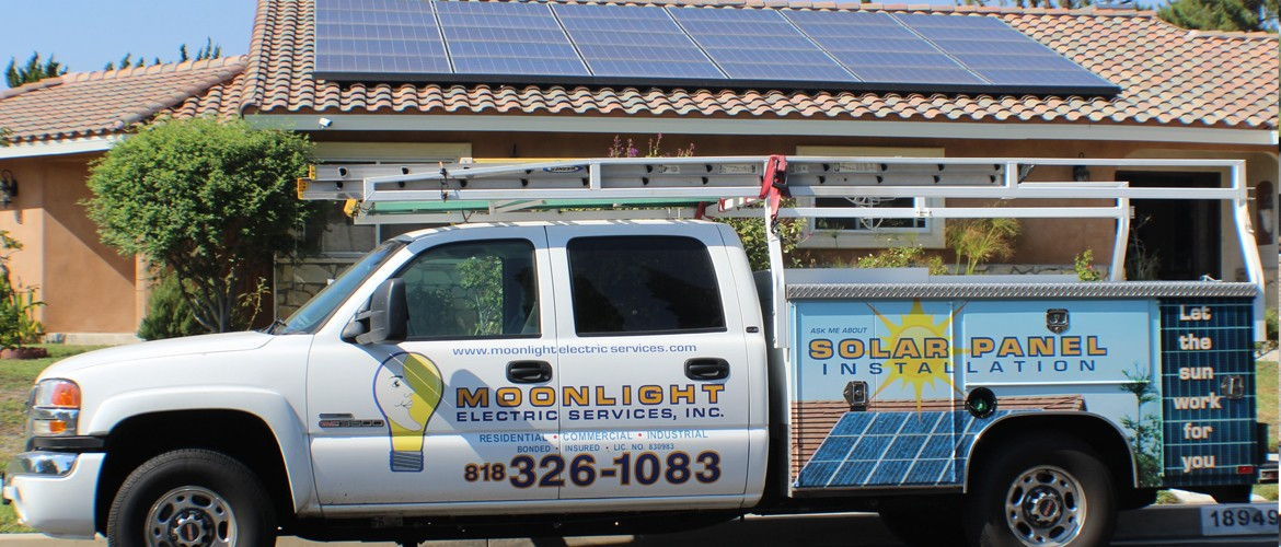 Moonlight Electric Services, Inc truck in parked in front of a solar panel installation site.