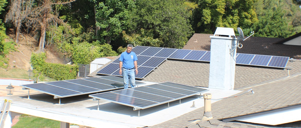 A Moonlight Electric technician on a roof checking out the installed solar panels.