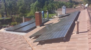 Solar panels installed on roof and on top of a patio cover.