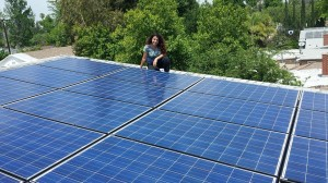 Ziva of Moonlight Electric Services, Inc. kneeling next to successfully installed solar panels.