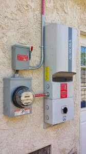 Solar inverter installed and attached to an electrical meter.