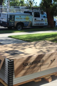 Box of solar panels and Moonlight Electric Services, Inc. truck parked out front.